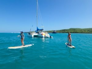 Sabrina and Alexandra on stand-up paddle boards, exploring San Cristobal, Aldebaran in the background